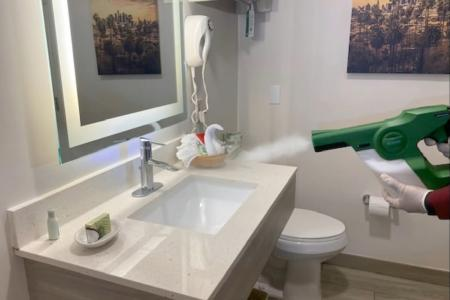 Disinfectant applied by electrostatic sprayer in guest bathroom